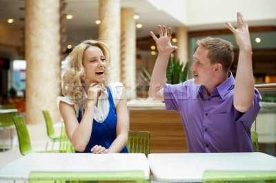 1505165_stock-photo-young-debating-or-talking-couple-inside-mall-sitting-near-the-ta
