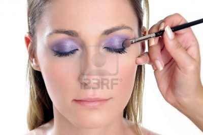 582386-young-woman-close-up-applying-violet-eye-shadow