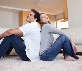Side view of couple sitting on the carpet back-to-back