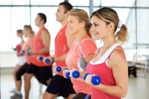 People doing exercise with dumbbells in the sport club.