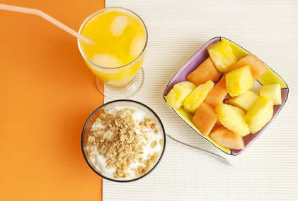 Breakfast consisting of yogurt, orange juice and fresh fruit